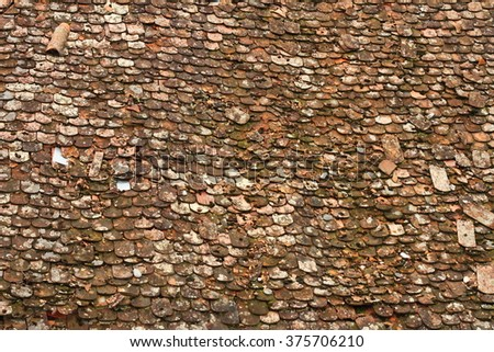 texture of old damaged roof with broken red tiles - stock photo