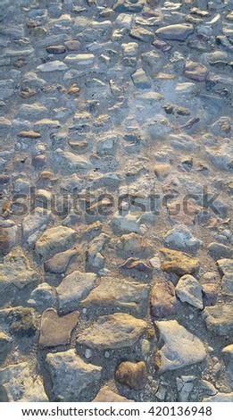 Texture of road surface paved with rough stones - stock photo