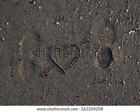 Texture of sand and heart,footprints in the sand - stock photo