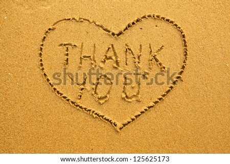 Texture of sand, the inscription inside the heart of Thank You.
