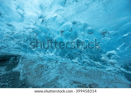 Texture of the ice wall inside the ice cave over the walk way - stock photo
