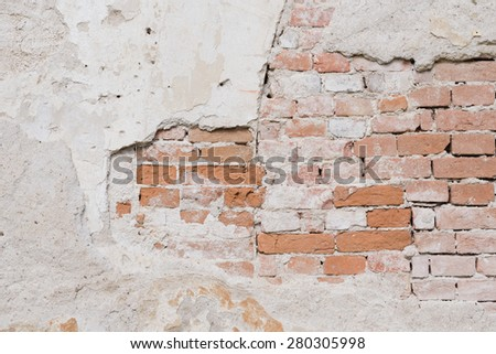 Texture of the old brick wall with damaged plaster - stock photo