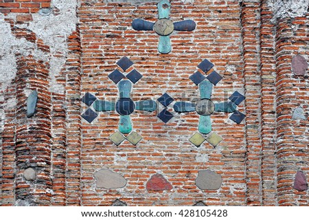 Texture of the old walls of clay brick, decorated with inserts of colored stones in the shape of crosses. Kalozha church, Grodno, Belarus.