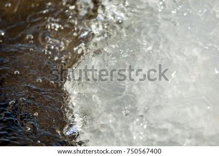 Texture of water ice stone. Water flowing turbulent flow in the mountains