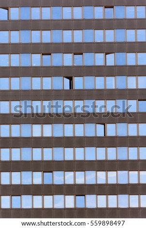 Texture windows on high-rise building. Reflection of the sky from the windows. The windows of an office building. Financial center.