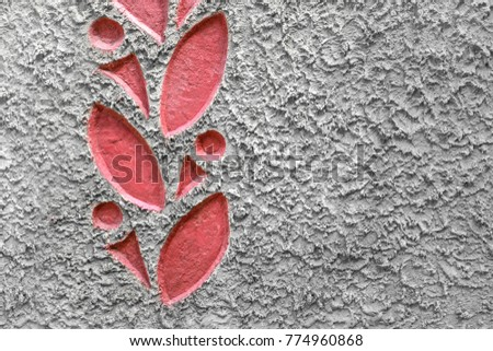 Textured background of cement with a pattern of red leaves on the border. Close-up.