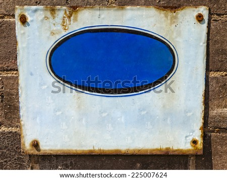 Textured  blue rusty metal background, with crude painted oval shape. Screwed to a grungy brick wall - stock photo