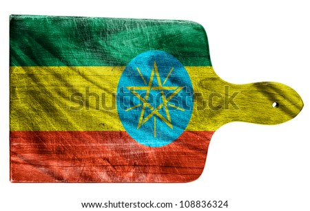 Textured Ethiopia flag painted on old heavily used chopping or cutting board on white background - stock photo