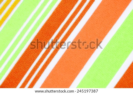 Textured fabric green orange and white.