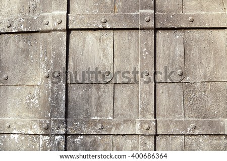 Textured metal painted surface with rust - aged hammered metal plates with rivets and stripes on the surface. Metal detailed background - stock photo