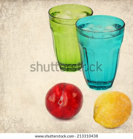 Textured old paper background with Color ripe plums and drink glasses with ice cooled drink (water) still life. Vintage style image  - stock photo