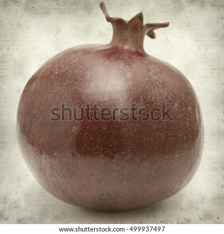 textured old paper background with dark red ripe pomegranate