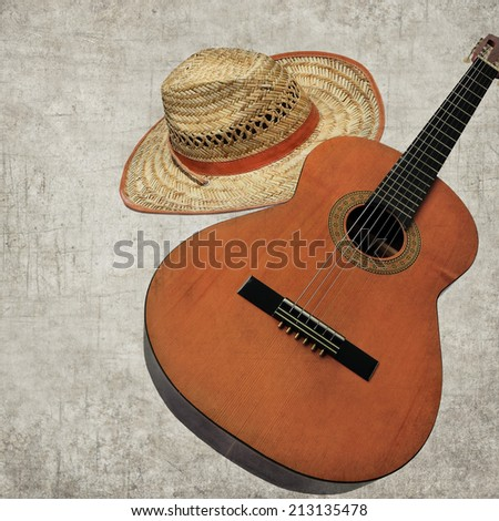 Textured old paper background with Guitar and old straw hat - Photo in retro style. Paper texture./Aged textured photo - stock photo
