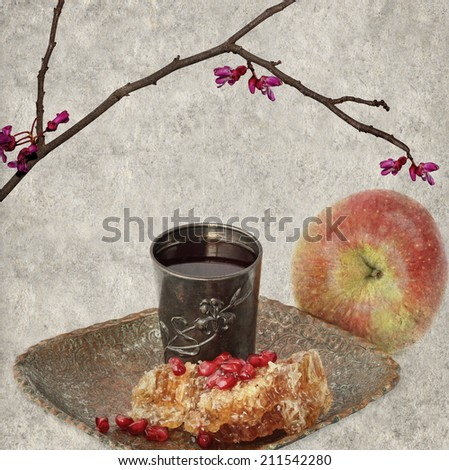 Textured old paper background with honey combs, pomegranate grains, silver glass with wine and apple fruit  - Jewish traditional food for the holiday of Rosh Hashana. Jewish New year retro still life. - stock photo