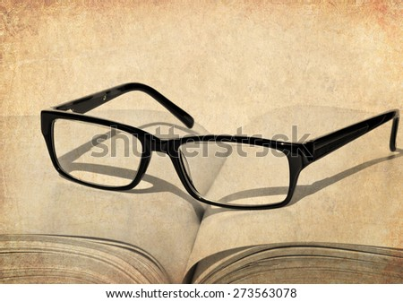 Textured old paper background with open book and eye glasses - stock photo