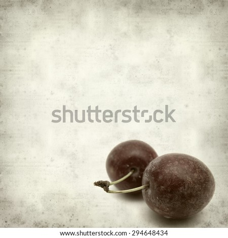 textured old paper background with small red plums
