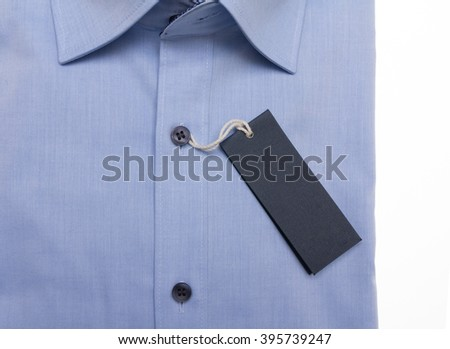 textured paper tag on blue man's shirt on white table at store
