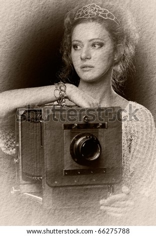 Textured retro photo of young woman standing near the old camera