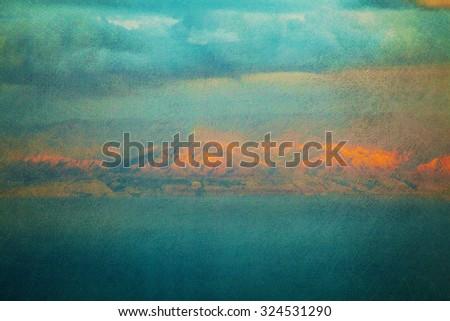 Textured vintage image of mountains glowing orange over sea at sunset (textured image, grunge effect, toning) - stock photo