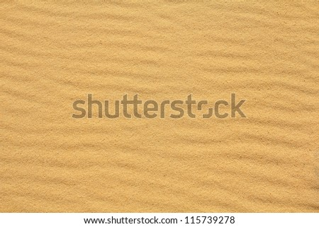 Textured wavy yellow sand all over the frame - stock photo