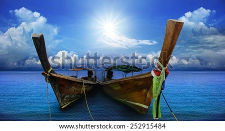 thai andaman long tailed boat southern of thailand on sea beach with beautiful sun shining over sky - stock photo