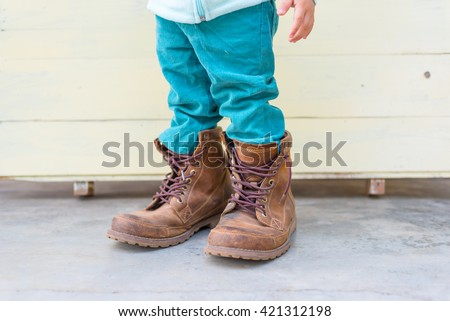Thai Baby boy try to  wearing father's boots - stock photo