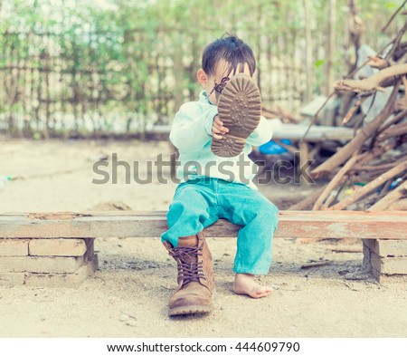 Thai Baby boy try to  wearing father's boots while drinking milk from bottle.  - stock photo