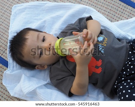 thai baby drinking milk from bottle on a reed mat in a park