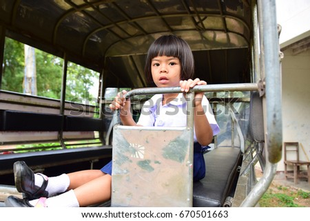 Thai baby girl in school uniform sit on pickup truck