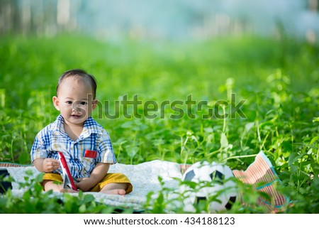 thai baby playing on grass in park