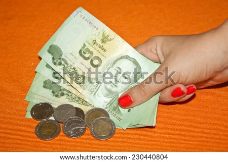 Thai baht - banknotes and coins in woman's hand - stock photo