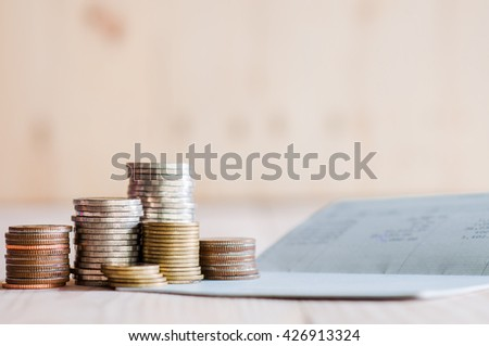 Thai banknotes and coins on book bank and account book background - stock photo