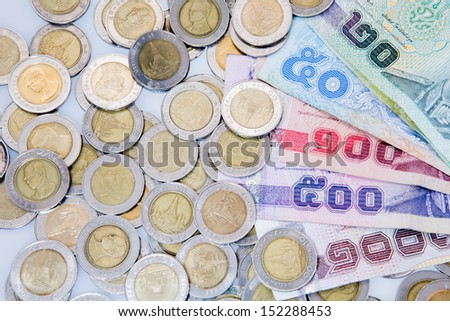 Thai banknotes and coins on white background