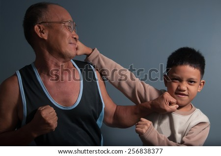 Thai boxing with a grand father and a kid on dark background in studio.