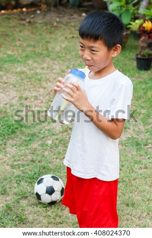 Thai boy drink cold water from plasctic bottle using straw. - stock photo