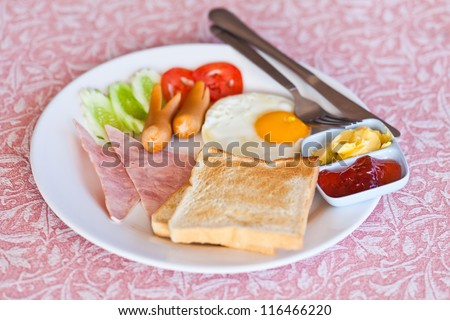 Thai breakfast with fried eggs, sausages, bread