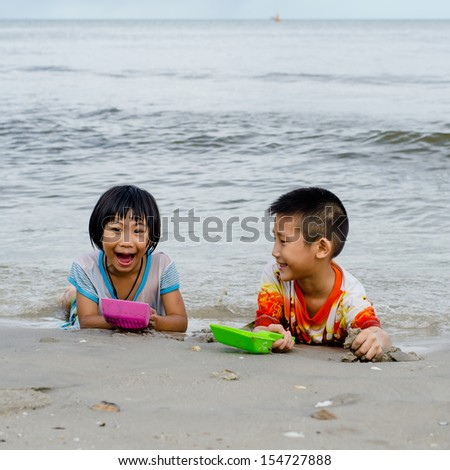 Thai brother and sister ages 6 and 4 have fun digging in the sand at the beach - stock photo