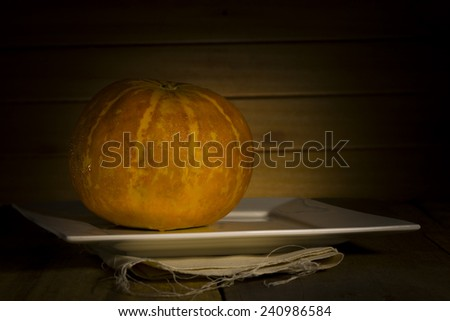Thai cantaloupe melon or sweet melon on a table in front of a wooden wall - stock photo