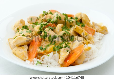 Thai coconut mango curry chicken with coconut rice and carrots and chopped cilantro on top for garnish - stock photo
