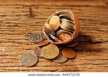 thai coin in broken egg on wooden background - stock photo