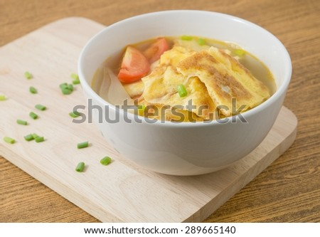 Thai Cuisine and Food, Thai Omelet Soup with Tomatoes, Onion and Chopped Scallion on Wooden Cutting Board. - stock photo