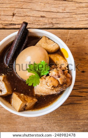 """Thai Cuisine called """"Kai Palo"""" , """"Khai Palo"""" or """"Pa-Lo"""",  Boiled eggs with chicken drumstick and fried tofu in sweet gravy soup seasonings top with coriander. / on wood table background, food rustic. - stock photo"""