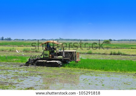 Thai farmer on small tractor with blue sky - stock photo