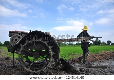 Thai farmer workers plows the paddy field using special tractor to prepare the seedbed - stock photo