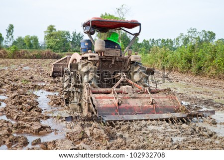 Thai farmers are using a tractor to prepare the soil for growing rice. - stock photo