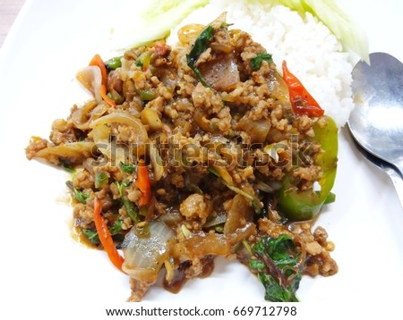 "Thai fast food is called ""fried pork basil"", put on a white plate and has a spoon."