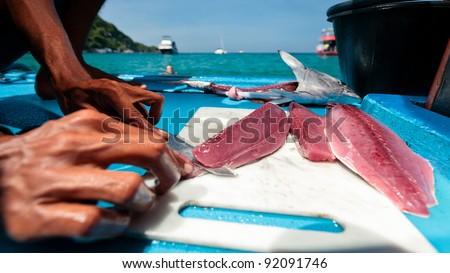 Thai Fishermen cleaning and filleting a fresh tuna aboard a deep sea fishing boat. Prepares tuna sashimi. - stock photo