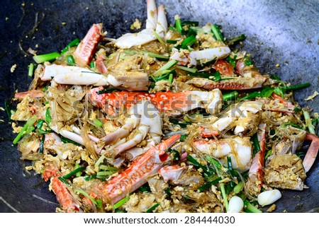 Thai Food (Boo Pad Pong Karee) : Sea Crab  stir fried  in Yellow Curry with Coconut Milk and cellophane noodle in pan - stock photo