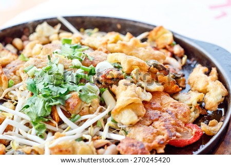 Thai food, fried mussel pancake in hot pan - stock photo