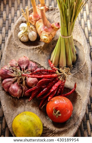Thai Food ingredient such as lemon grass, galangal, garlic, red onion,Dried chilli   in a wood tray/Thai Food ingredient/Thai Food basic ingredients in a wood tray - stock photo